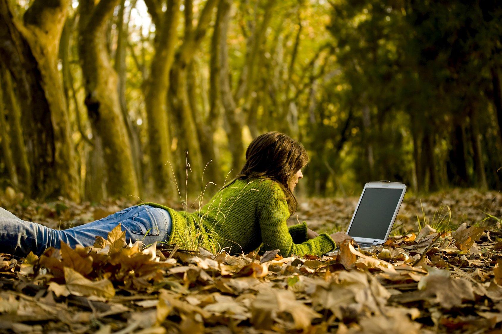 Frau arbeitet im Herbstwald am Laptop